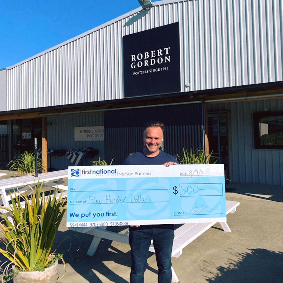 Man holding massive cheque at Robert Gordon Pottery