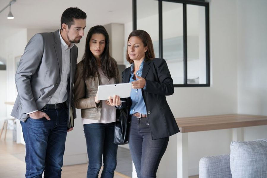 Couple inspecting a property with real estate agent