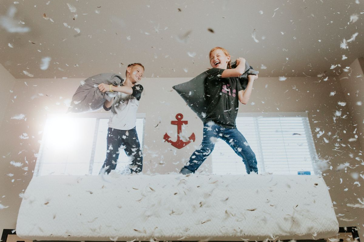 Boys having a pillow fight on a bed