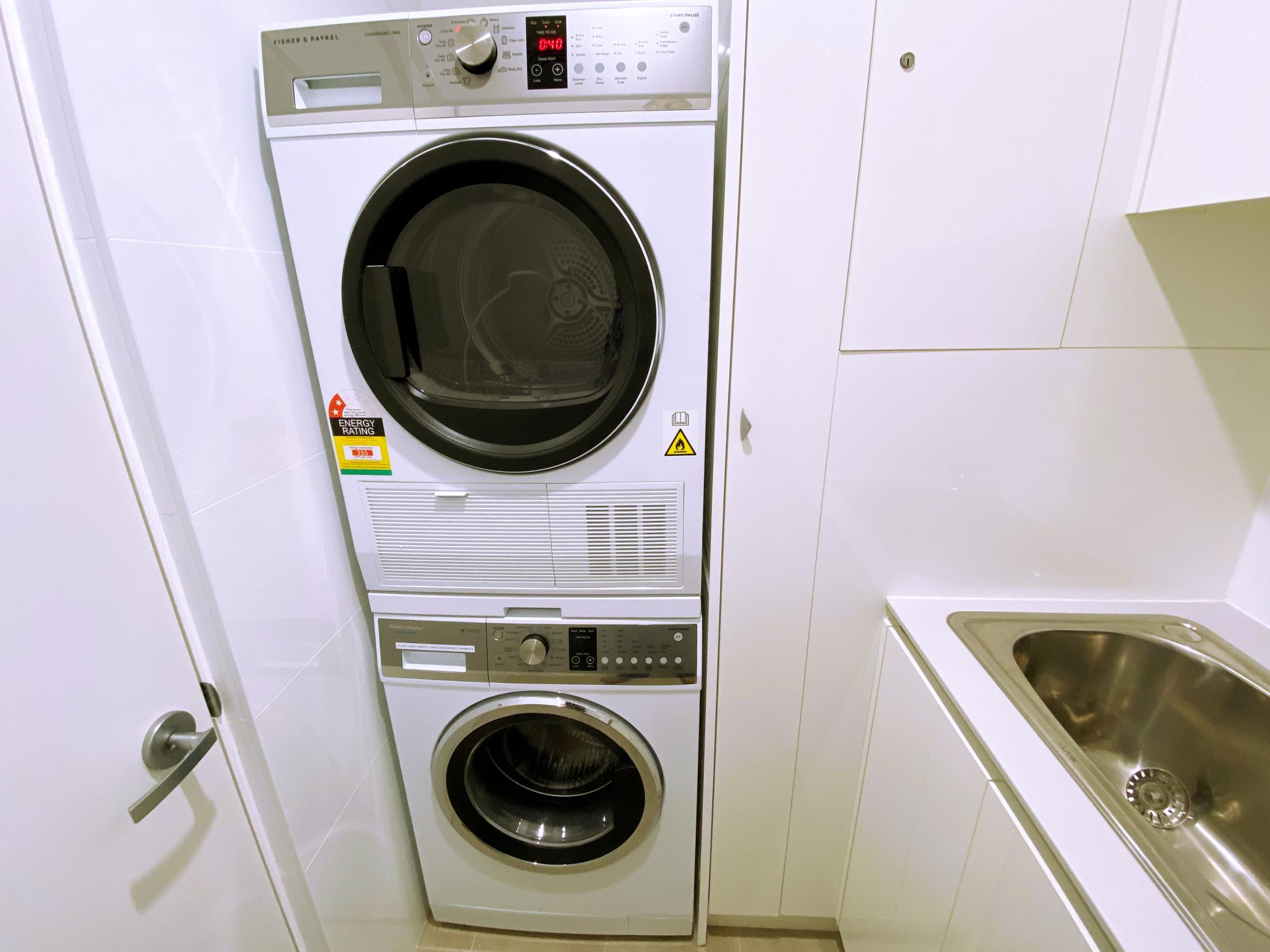 Private laundry in apartment with tumble dryer & front loading washing machine.